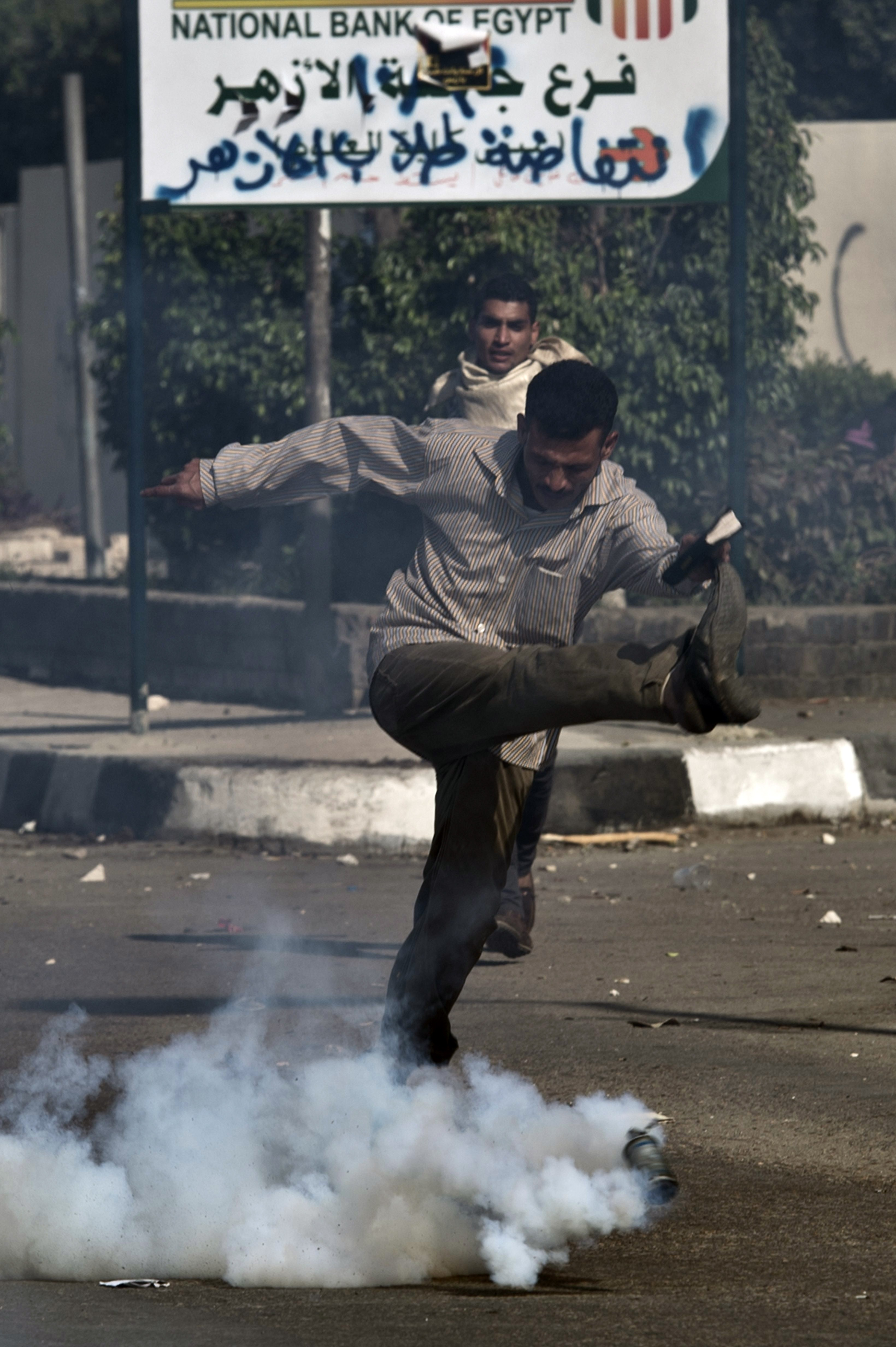 An Egyptian student of al-Azhar university kicks a tear gas canister fired by riot police during clashes outside their university campus in Cairo on October 20, 2013 following an anti-army protest. (AFP PHOTO / KHALED DESOUKI)