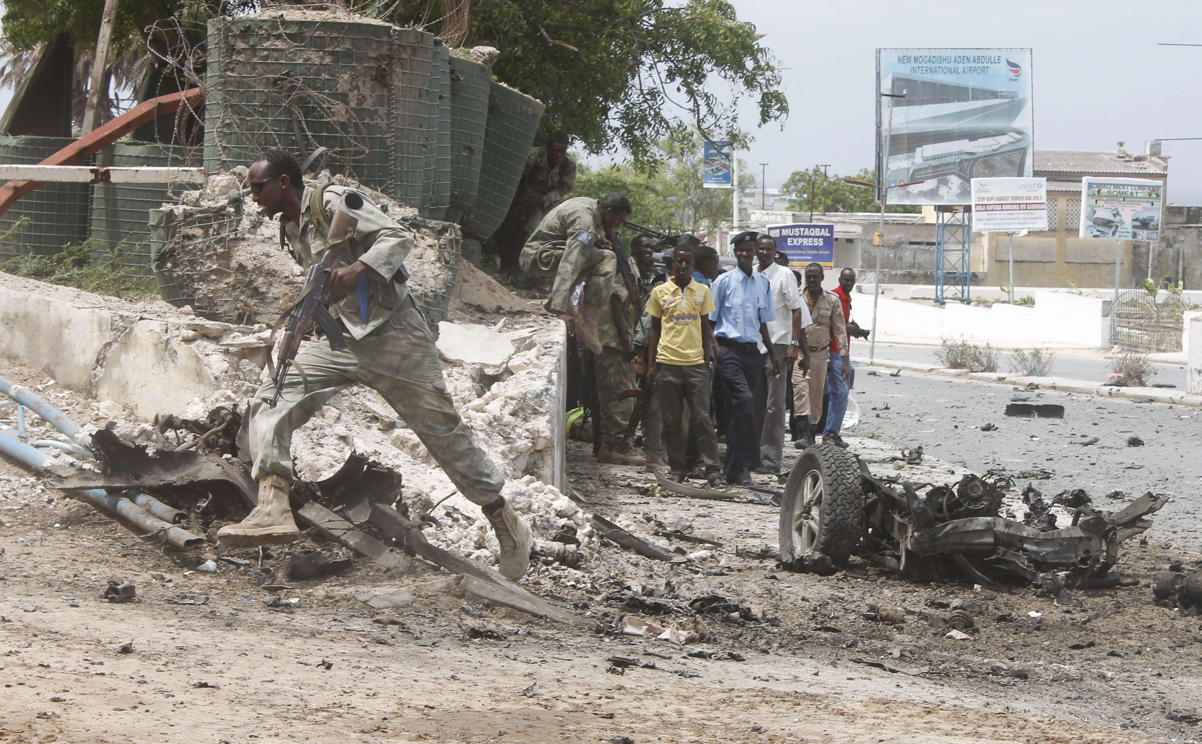 A Somali army soldier runs towards the Somali parliament as other take cover during an attack, in Mogadishu, on May 24, 2014. Somalia's Shebab rebels launched a major attack on the national parliament today, setting off a car bomb and penetrating the building with suicide commandos, leaving at least eight dead, police and witnesses said.   (AFP PHOTO / Mohamed Abdiwahab)
