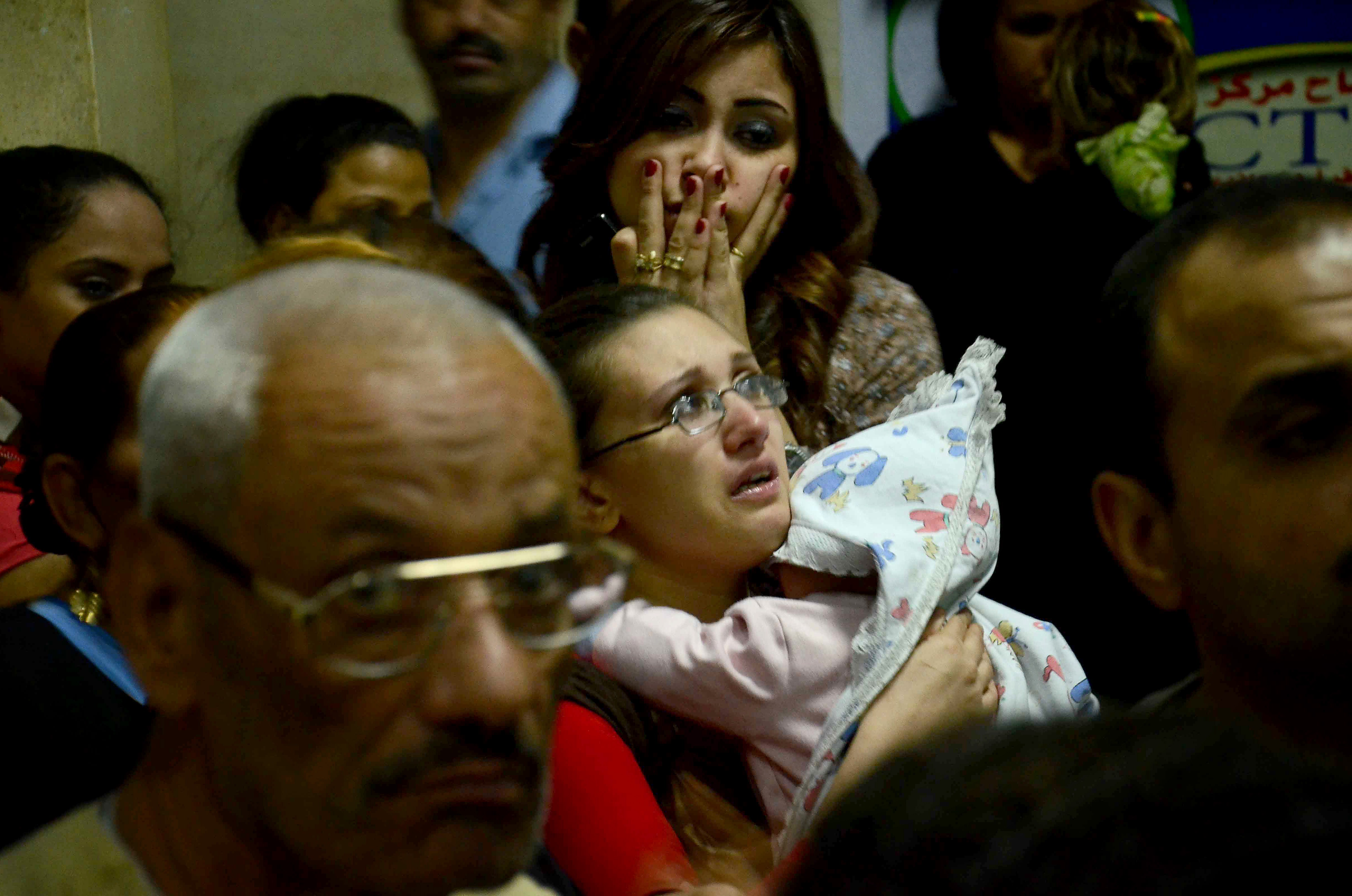 Egyptian women, some in tears, gather inside the Virgin Mary Coptic Christian church in Cairo after gunmen on a motorbike shot dead several people.   AFP PHOTO /