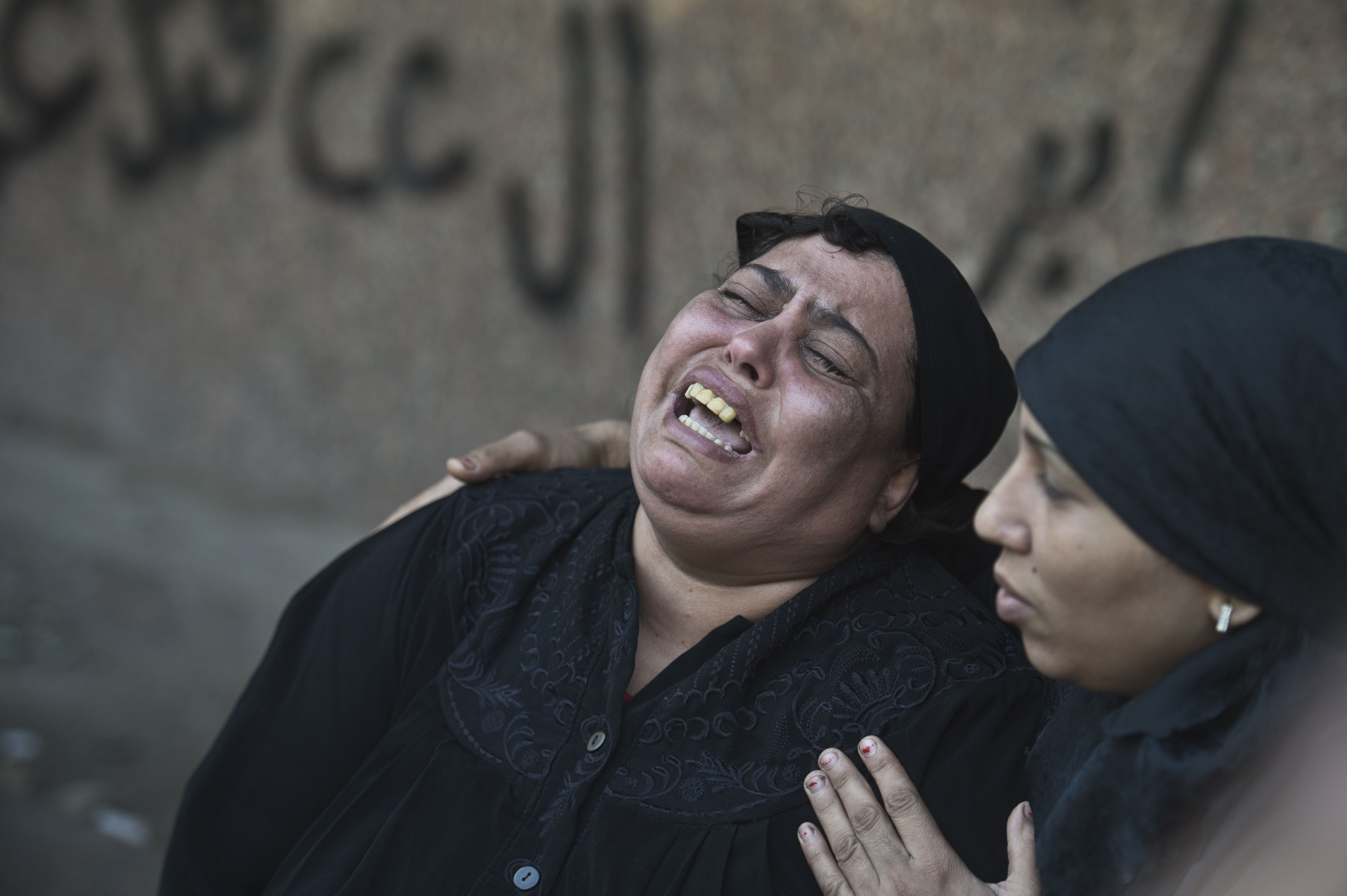 An Egyptian relative of one of the victims of a shooting spree targeting a wedding at a Cairo Coptic Church is comforted as she mourns at a morgue in the capital on October 21, 2013. Late on October 20, a gunman riding on the back of a motorbike sprayed bullets at a group as it emerged from a wedding service at the Church of the Virgin in the working class neighbourhood of Al-Warrak. (AFP PHOTO / KHALED DESOUKI)
