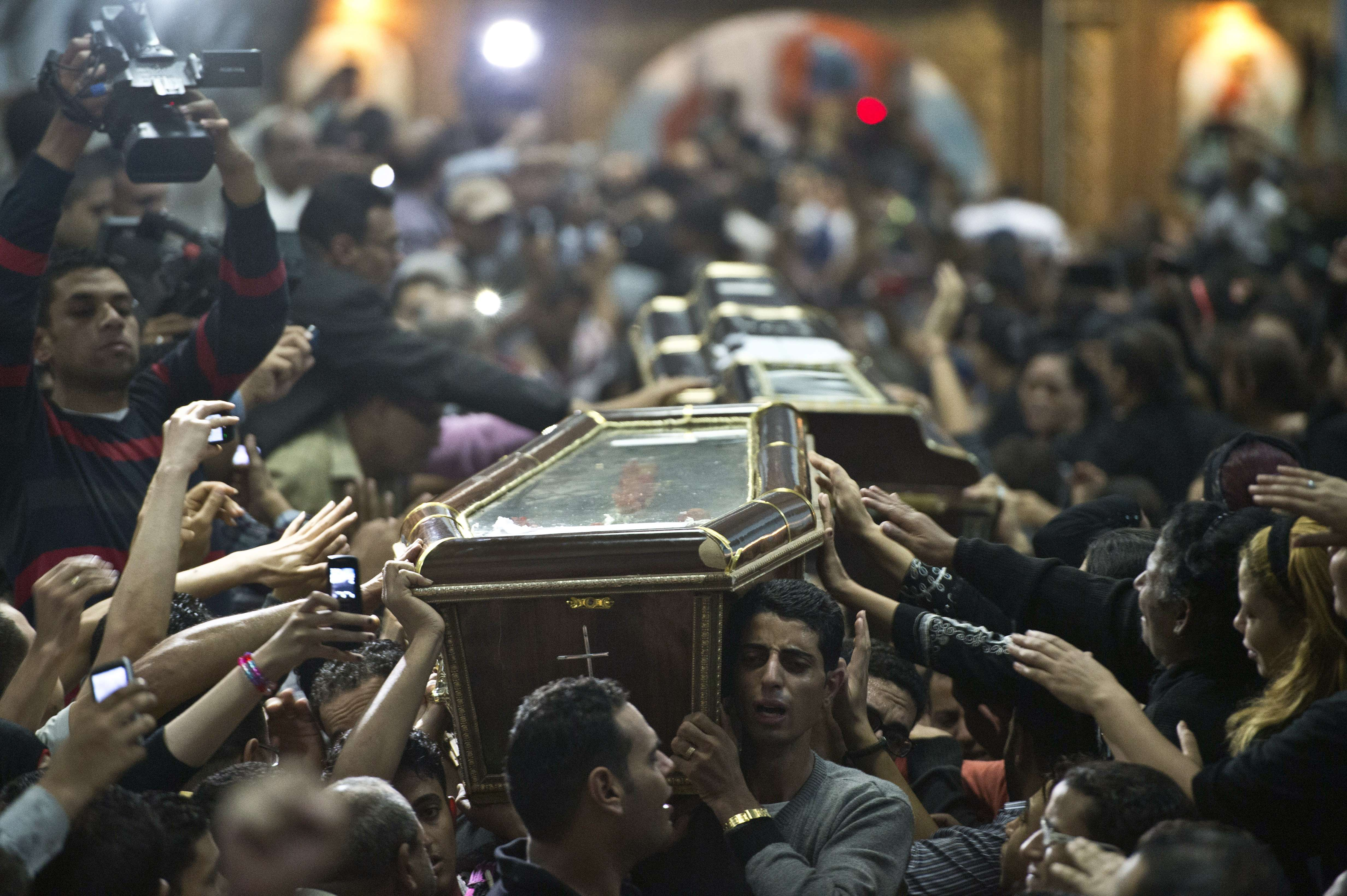 Egyptian Copts carry four coffins down the aisle of the Virgin Mary Coptic Christian church in Cairo's working class neighbourhood of Al-Warrak, on October 21, 2013, as thousands attend the funeral of the victims, gunned down as they attended a wedding the previous evening at the same church.  (AFP PHOTO / KHALED DESOUKI)