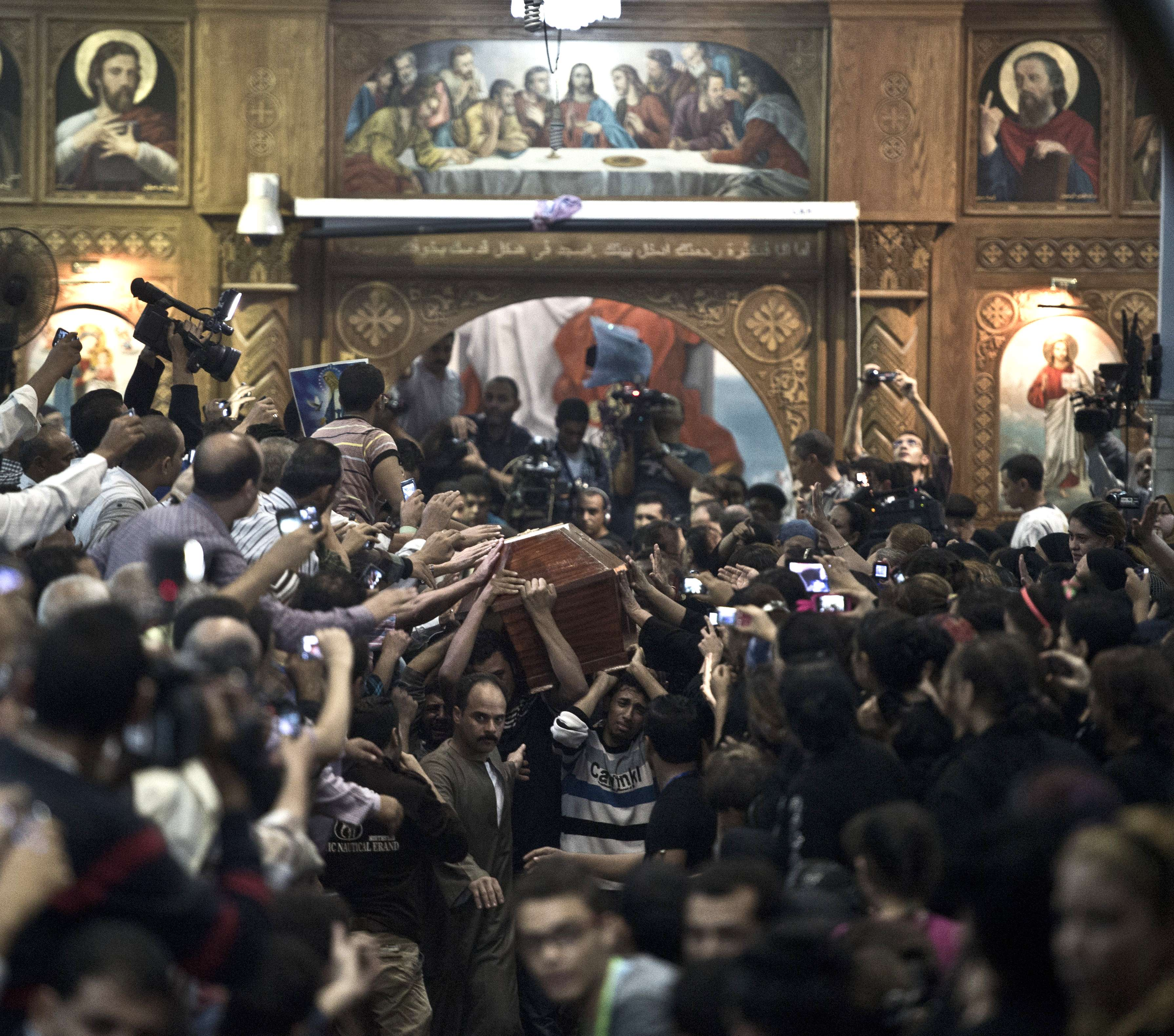 Egyptian Copts carry one of four coffins down the aisle of the Virgin Mary Coptic Christian church in Cairo's working class neighbourhood of Al-Warrak, on October 21, 2013, as thousands attend the funeral of the victims, gunned down as they attended a wedding the previous evening at the same church.  ( AFP PHOTO / KHALED DESOUKI)