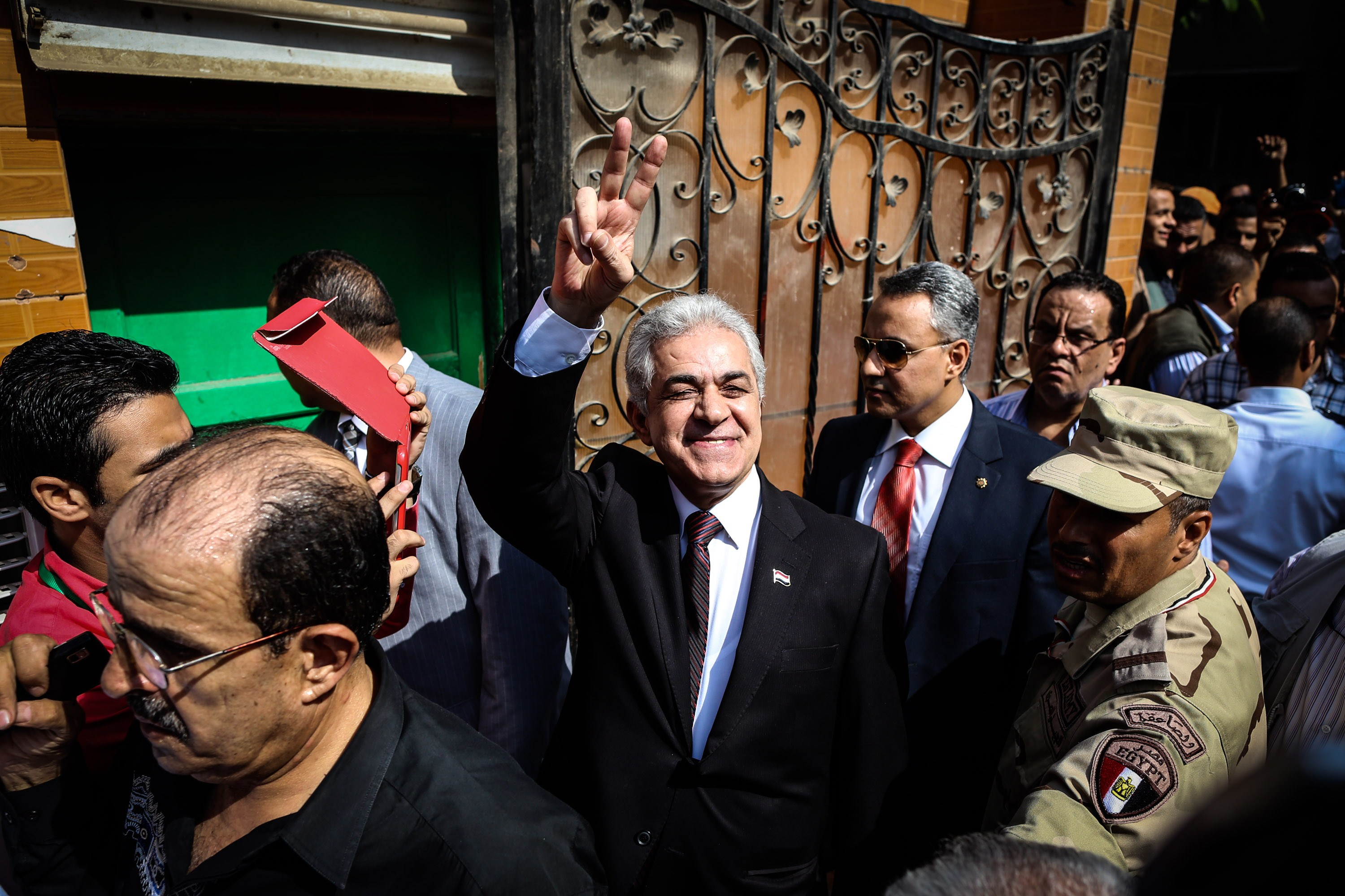 Egyptian presidential candidate Hamdeen Sabahi (C) gestures to his supporters after casting his vote at a polling station in the capital Cairo on May 26, 2014. Egyptians voted for a new president, with the ex-army chief who overthrew the country's first democratically elected leader and crushed his Islamist movement expected to win in a landslide.  (AFP PHOTO/MOHAMED EL-SHAHED)