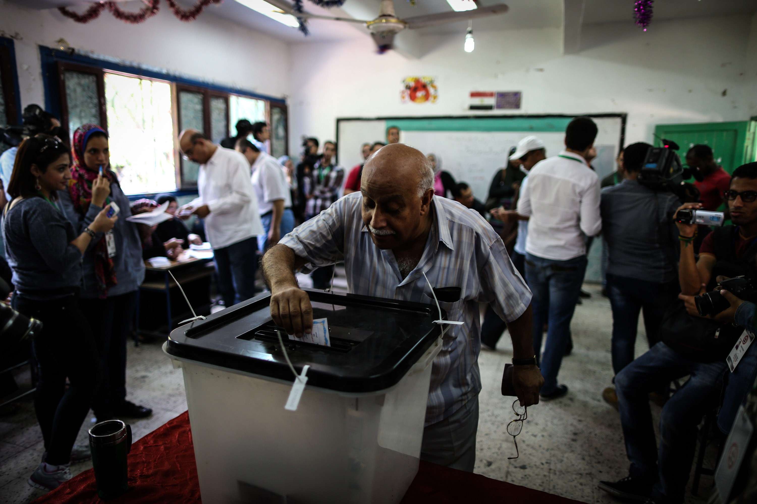 An Egyptian man casts his vote at a polling station in the capital Cairo on May 26, 2014. Egyptians voted for a new president, with the ex-army chief who overthrew the country's first democratically elected leader and crushed his Islamist movement expected to win in a landslide.  (AFP PHOTO/MOHAMED EL-SHAHED)