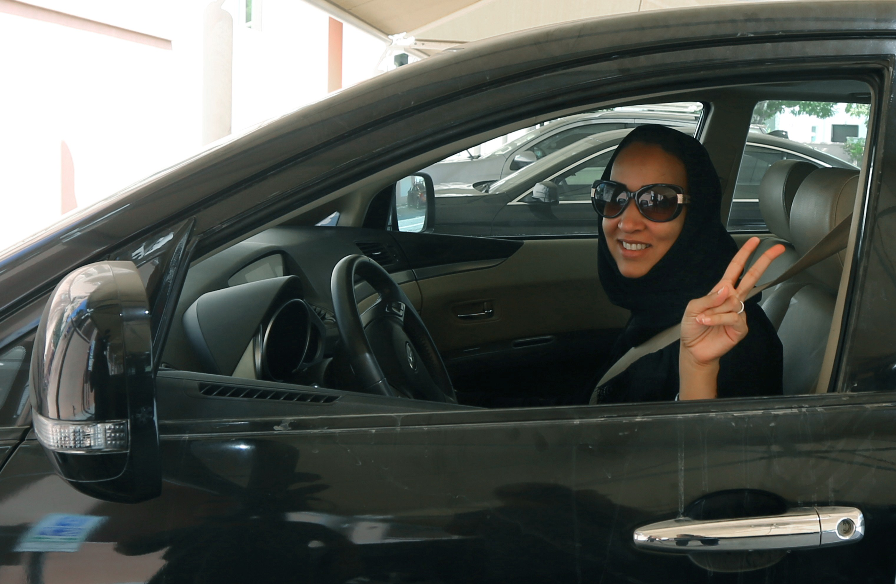 Saudi activist Manal Al Sharif, who now lives in Dubai, flashes the sign for victory as she drives her car in the Gulf Emirate city on 22 October in solidarity with Saudi women preparing to take to the wheel on 26 October (AFP Photo)