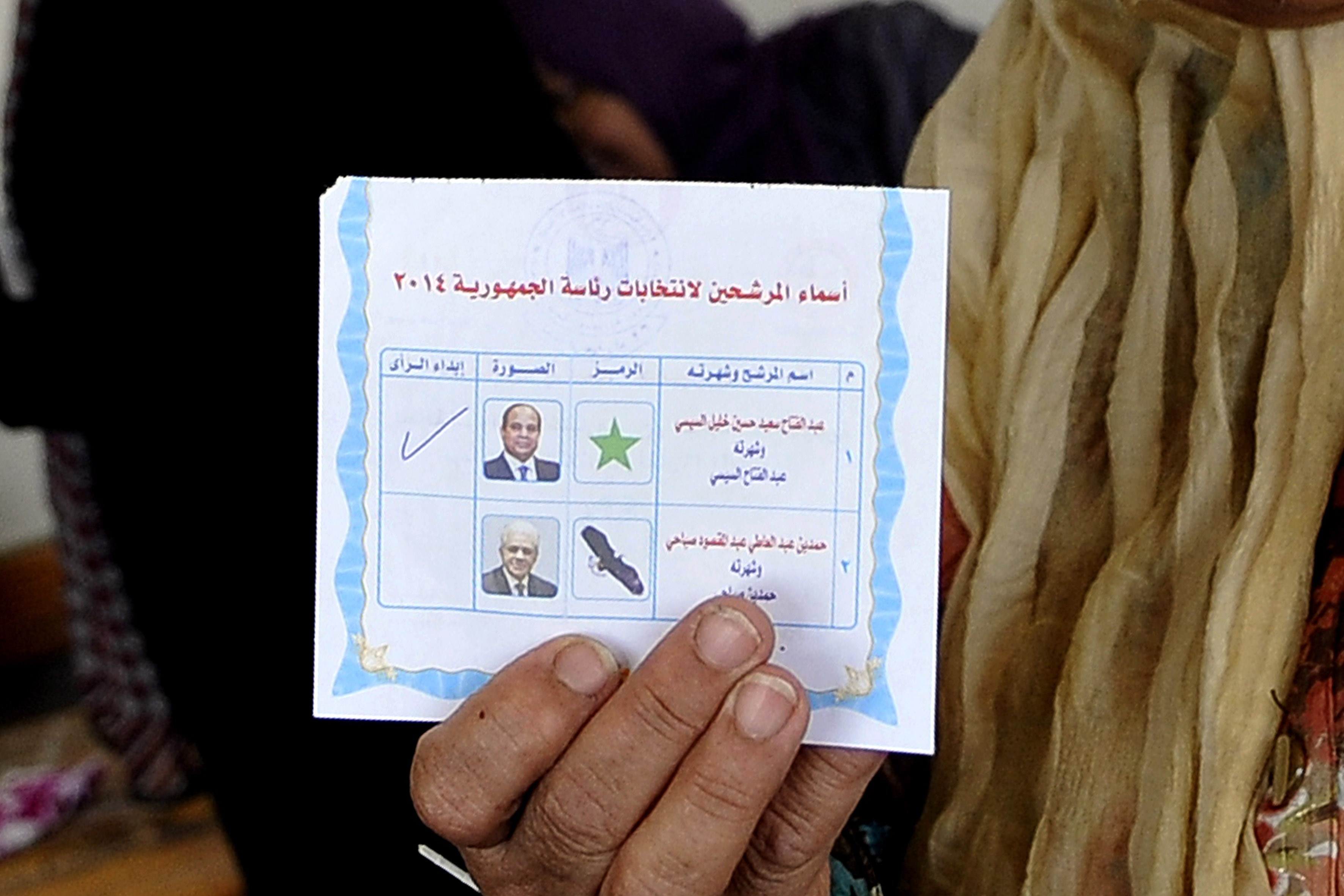 An Egyptian woman displays her ballot card at a polling station in the Mediterranean port city of Alexandria on May 26, 2014. Former defence minister Abdel Fattah Al-Sisi was elected president by 96.9% of valid votes, totaling 23,780,104, beating the only other contender, Nasserist politician Hamdeen Sabahy. (AFP PHOTO/ STR)