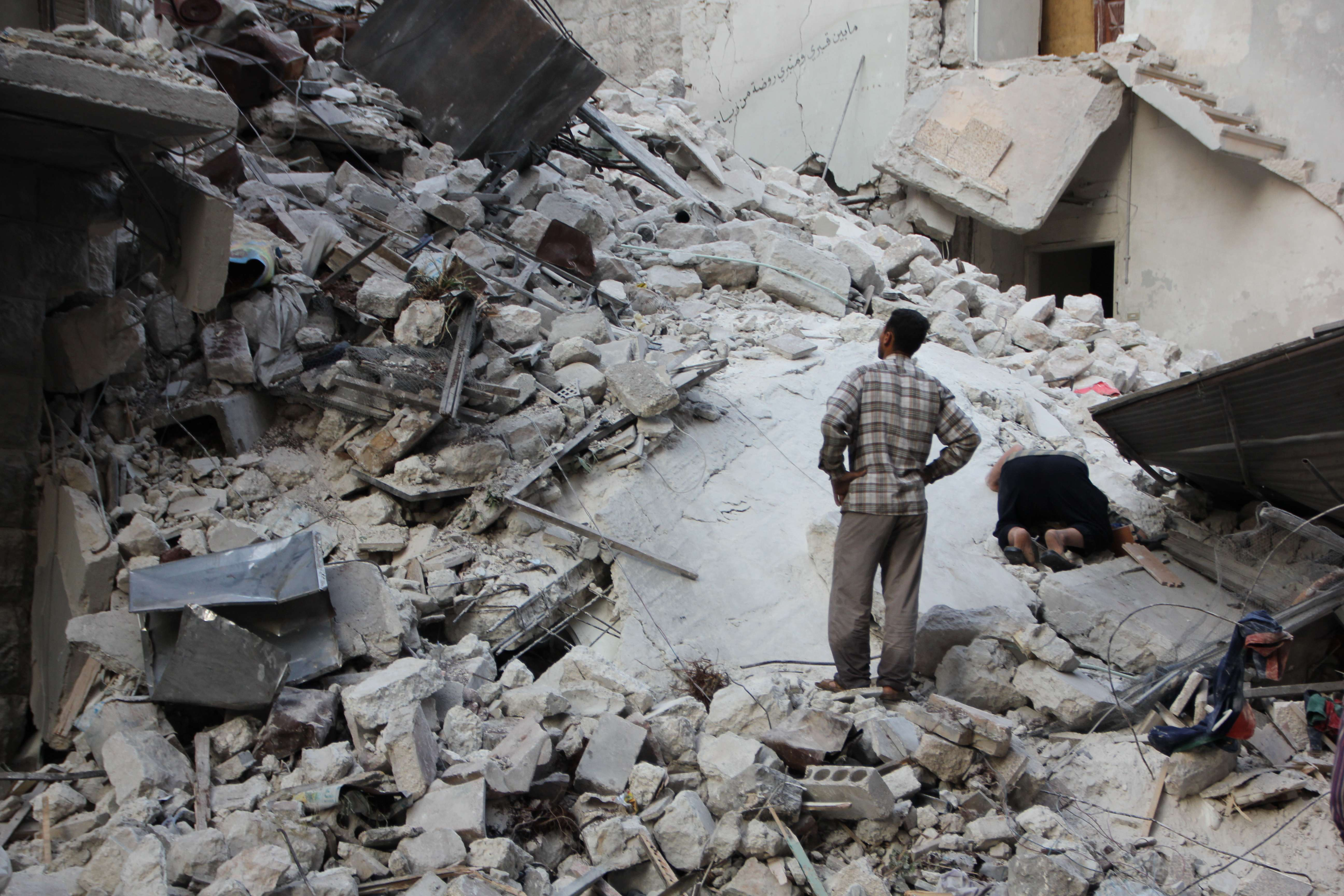 Syrian men search the rubble for survivors in a destroyed building following reported barrel bomb strikes by Syrian government forces on May 26, 2014 in the northern Syrian city of Aleppo. Syrian President Bashar al-Assad, facing two little-known challengers in a June 3 presidential election, is widely expected to clinch a third seven-year term despite Syria's civil war, which has killed more than 160,000 people.  (AFP PHOTO / BARAA AL-HALABI)