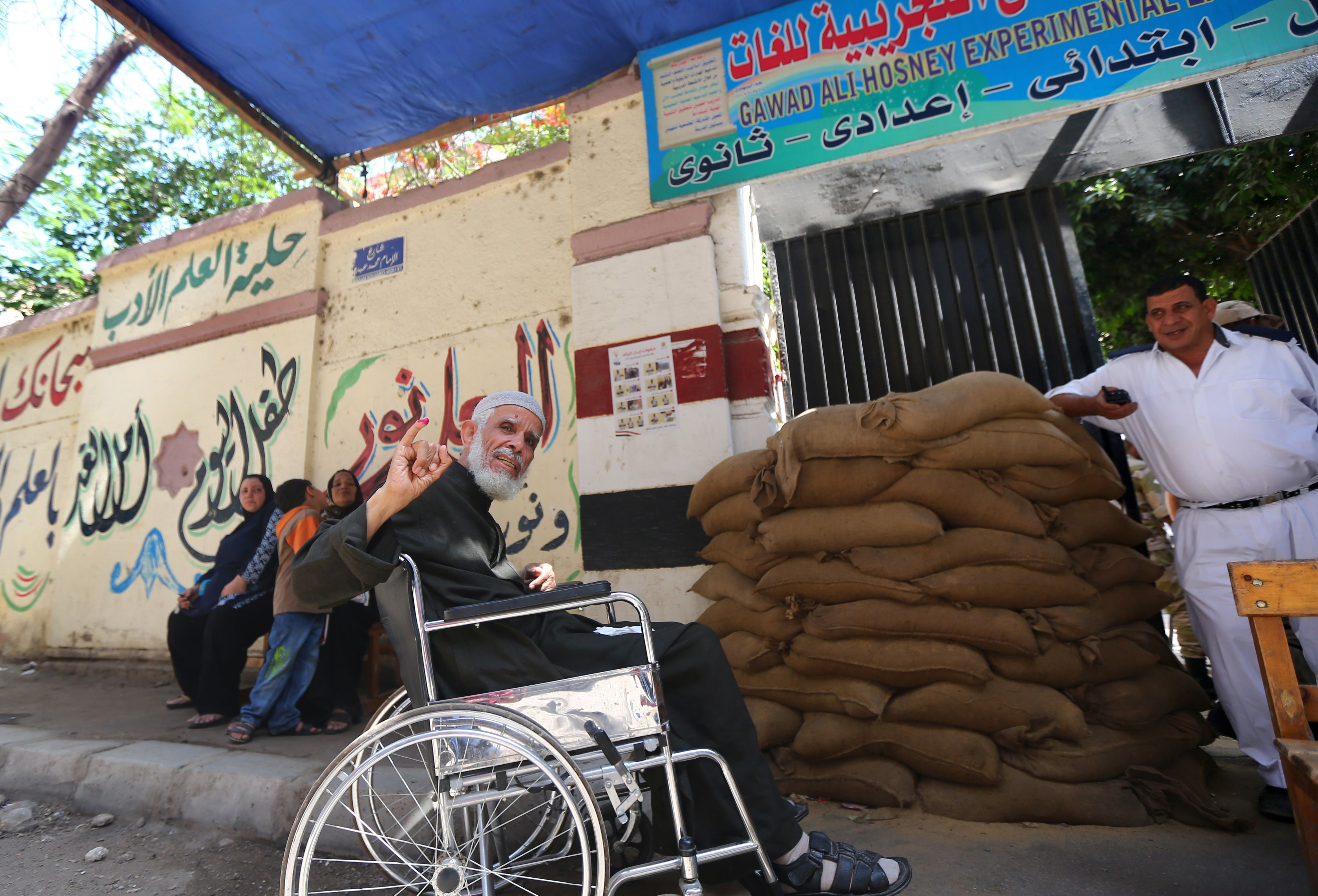 An Egyptian man using a wheelchair shows his ink-stained finger after casting his vote at a polling station in Cairo on the second day of Egypt's presidential election on May 27, 2014. The frontrunner is Abdel Fattah al-Sisi, the now retired army chief who ousted elected president Mohamed Morsi last July, in what many here call a bloody military coup.  (AFP PHOTO/MARWAN NAAMANI)