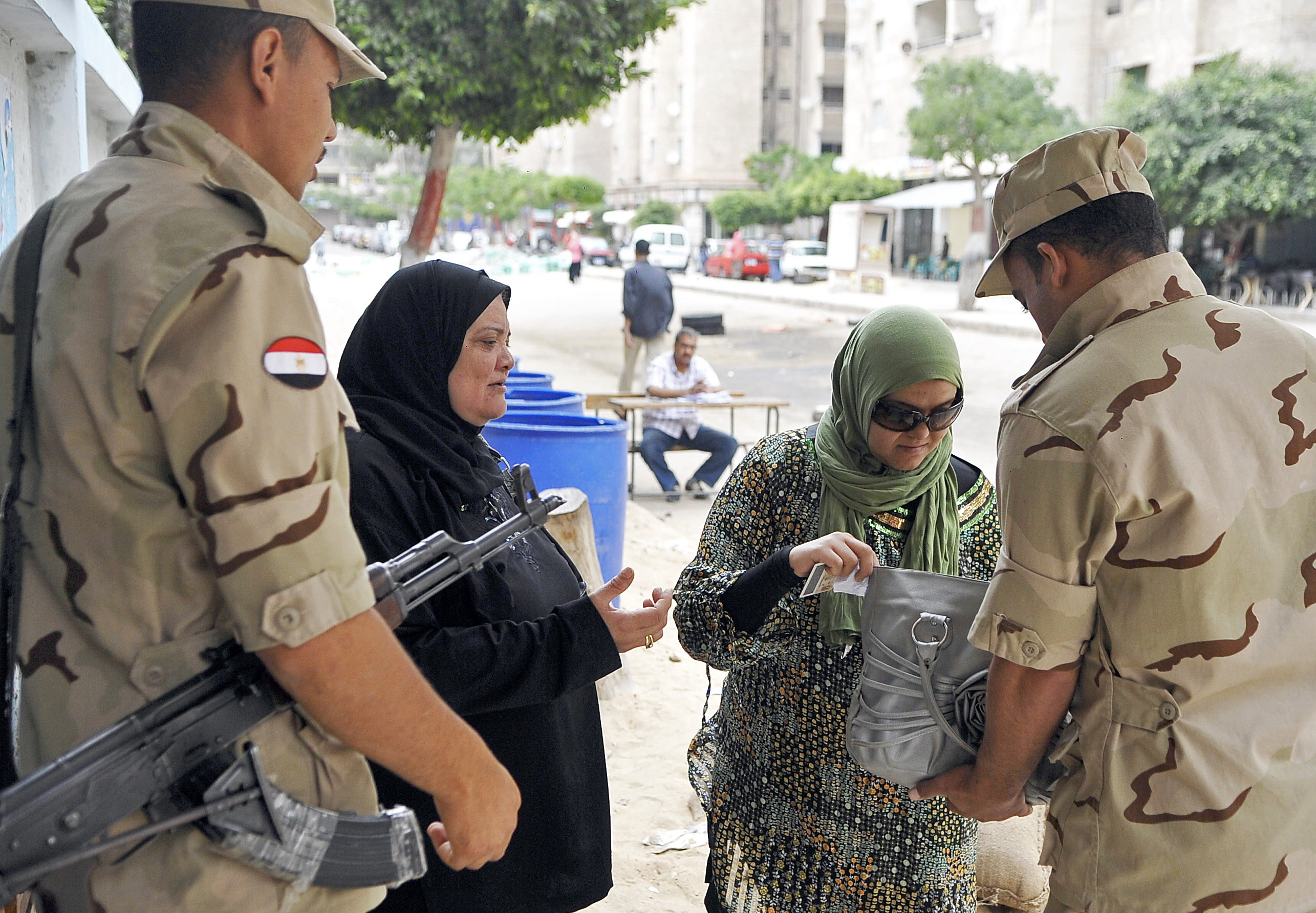 Egyptian security forces check a woman's bag outside a polling station as she arrives to cast her vote in Egypt's northern coastal city of Alexandria on May 28, 2014 after the electoral commission extended a presidential vote for a third day, amid reports of a low turnout in the first poll after the overthrow of Islamist leader Mohamed Morsi, state media said. About 37 percent of Egypt's eligible voters cast ballots in two days of presidential elections, an electoral official said.  (AFP PHOTO / STR)