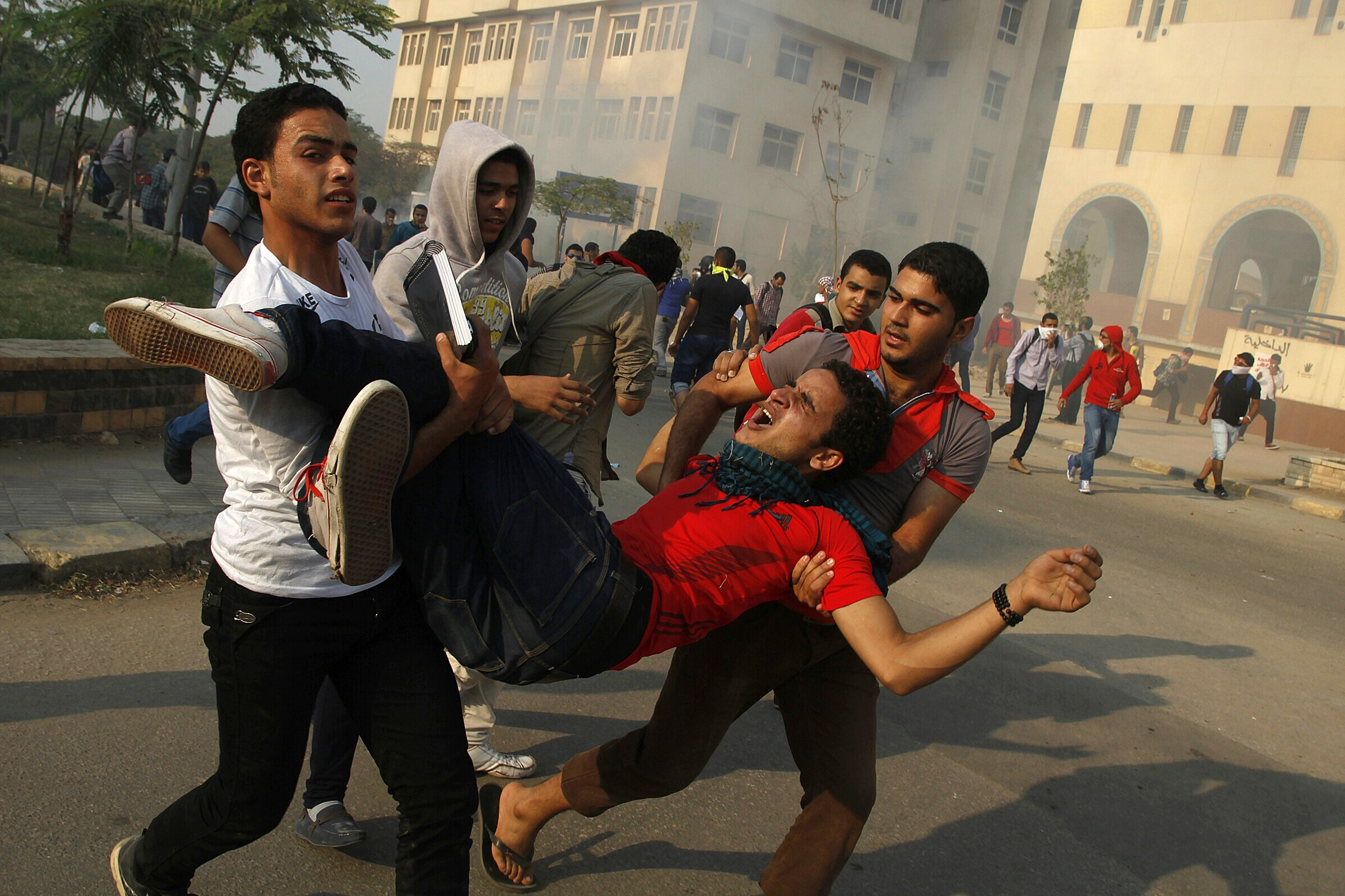 Student supporters of ousted president Mohamed Morsi and the Muslim brotherhood carry a comrade injured during clashes with Egyptian security forces outside their university camps in Cairo on October 28, 2013. (AFP PHOTO/MOHAMMED ABDEL MONEIM)