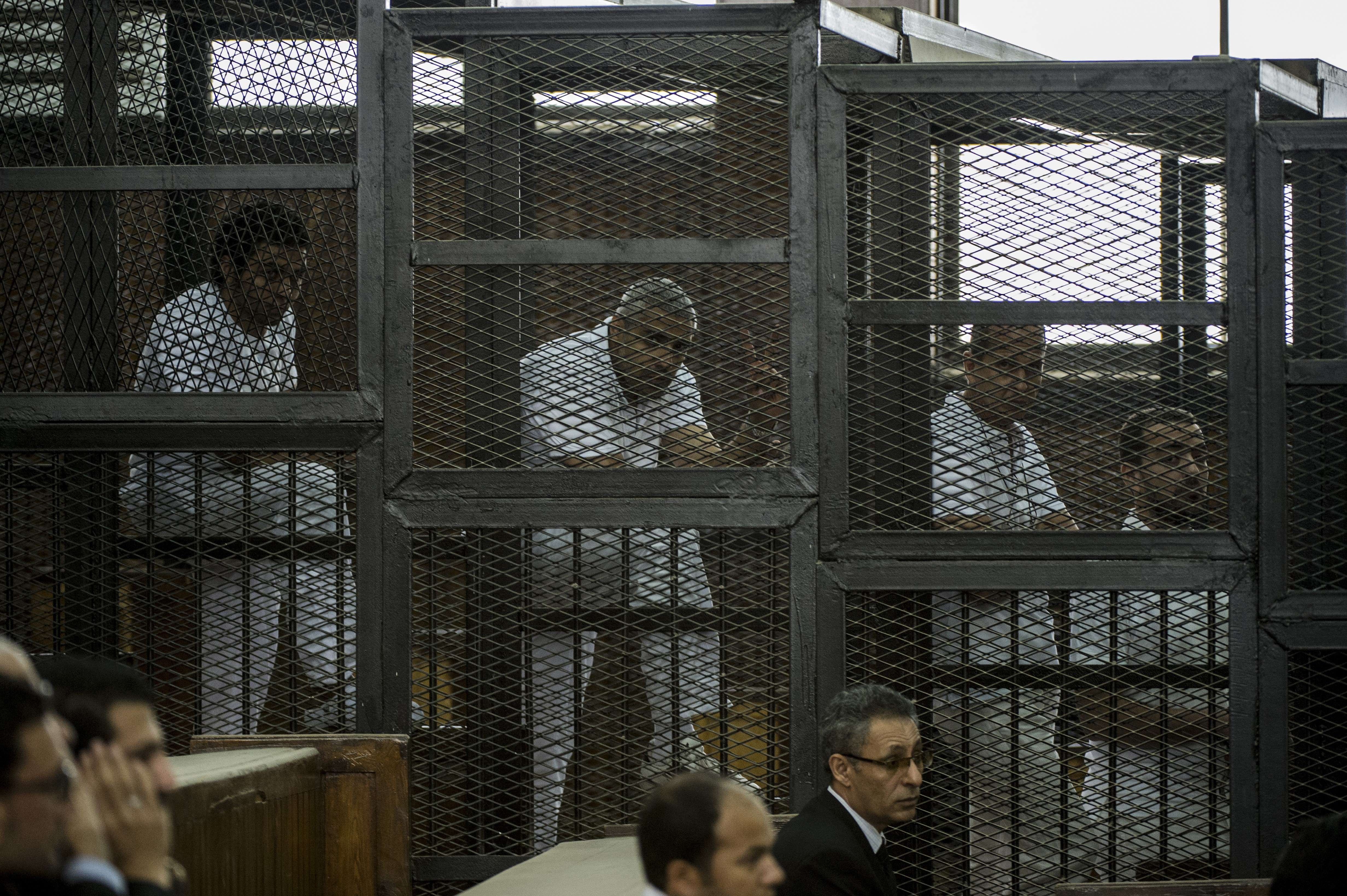 Al-Jazeera channel's Australian journalist Peter Greste (2nd-R), Egyptian-Canadian journalist Mohamed Fahmi (2n-L) and Egyptian journalist Mohamed Baher (R) stand inside the defendants cage during their trial for allegedly supporting the Muslim Brotherhood at the police institute near Cairo's Tora prison on June 1, 2014. The high-profile case that sparked a global outcry over muzzling of the press is seen as a test of the military-installed government's tolerance of independent media, with activists fearing a return to autocracy three years after the Arab Spring uprising that toppled Hosni Mubarak.  (AFP PHOTO / KHALED DESOUKI)