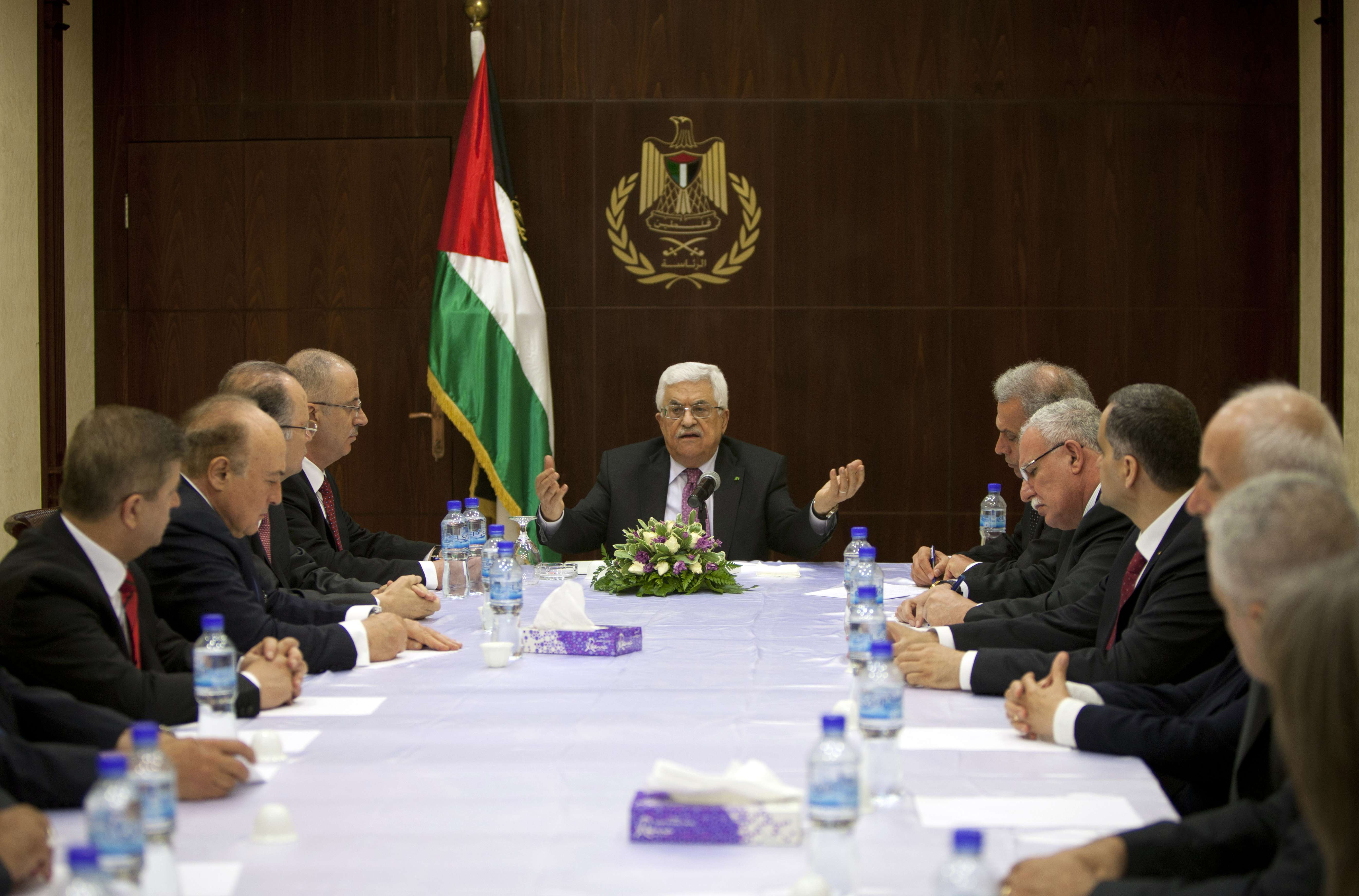 "Palestinian president Mahmud Abbas (R) chairs the first meeting of the new Palestinian unity government in the West Bank city of Ramallah June 2, 2014. Abbas hailed the ""end"" of Palestinian division as a new government took its oath under a unity deal between leaders in the West Bank and Gaza.  (AFP PHOTO/POOL/MAJDI MOHAMMED)"