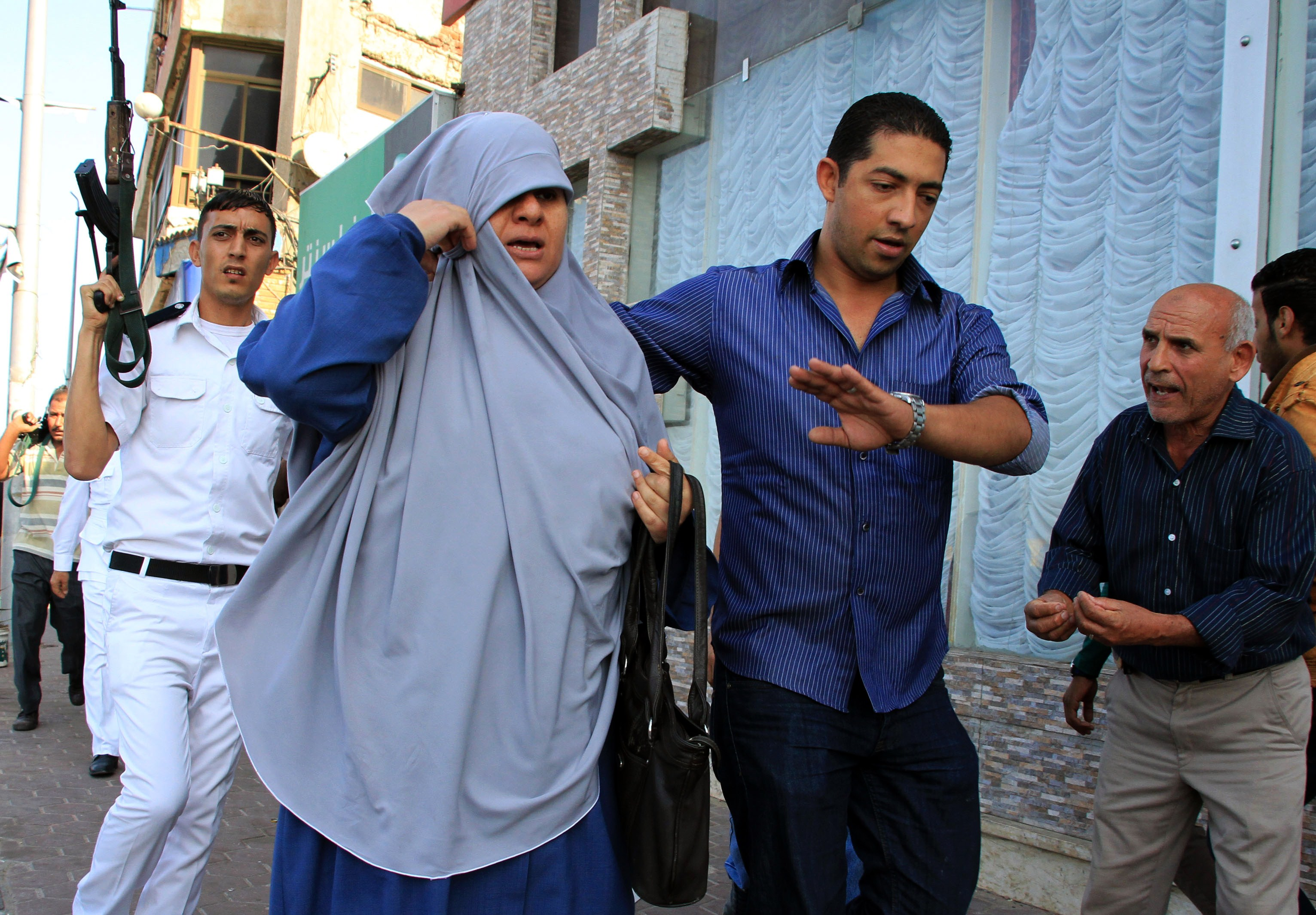 Plain clothes police arrest a woman as Islamists hold a protest in the Mediterranean Egyptian city of Alexandria ahead of the start of the trial of deposed president Mohamed Morsi on November 1, 2013.  (AFP Photo)