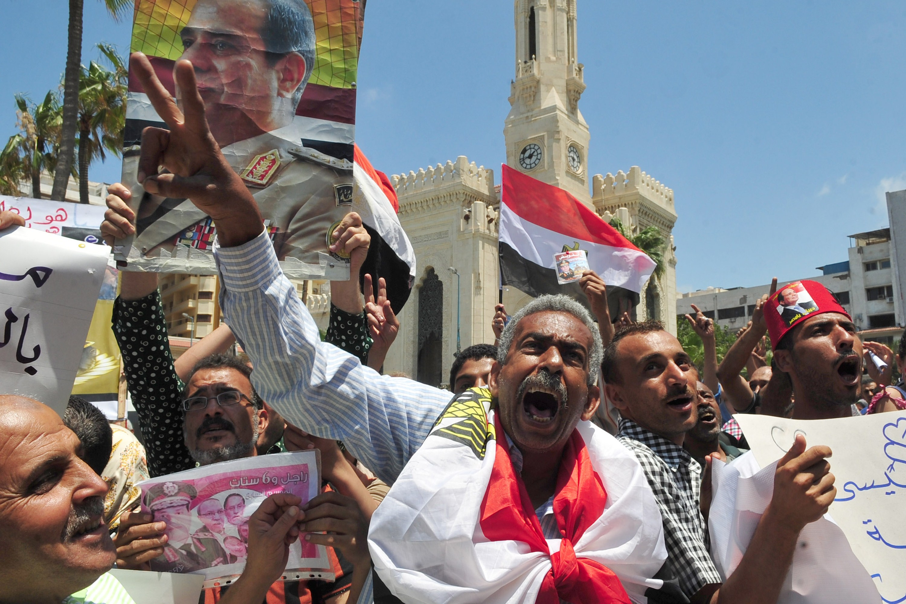 Egyptian protesters shout slogans and hold portraits of Egypt's new President Abdel Fattah al-Sisi on June 6, 2014, during a demonstration to show him their support, in the Mediterranean port city of Alexandria. On June 3, the electoral commission declared Sisi won 96.91 percent of the vote with a turnout of 47.5 percent, nearly a year after he toppled the country's first freely elected leader, Islamist Mohamed Morsi.  (AFP PHOTO / STR)