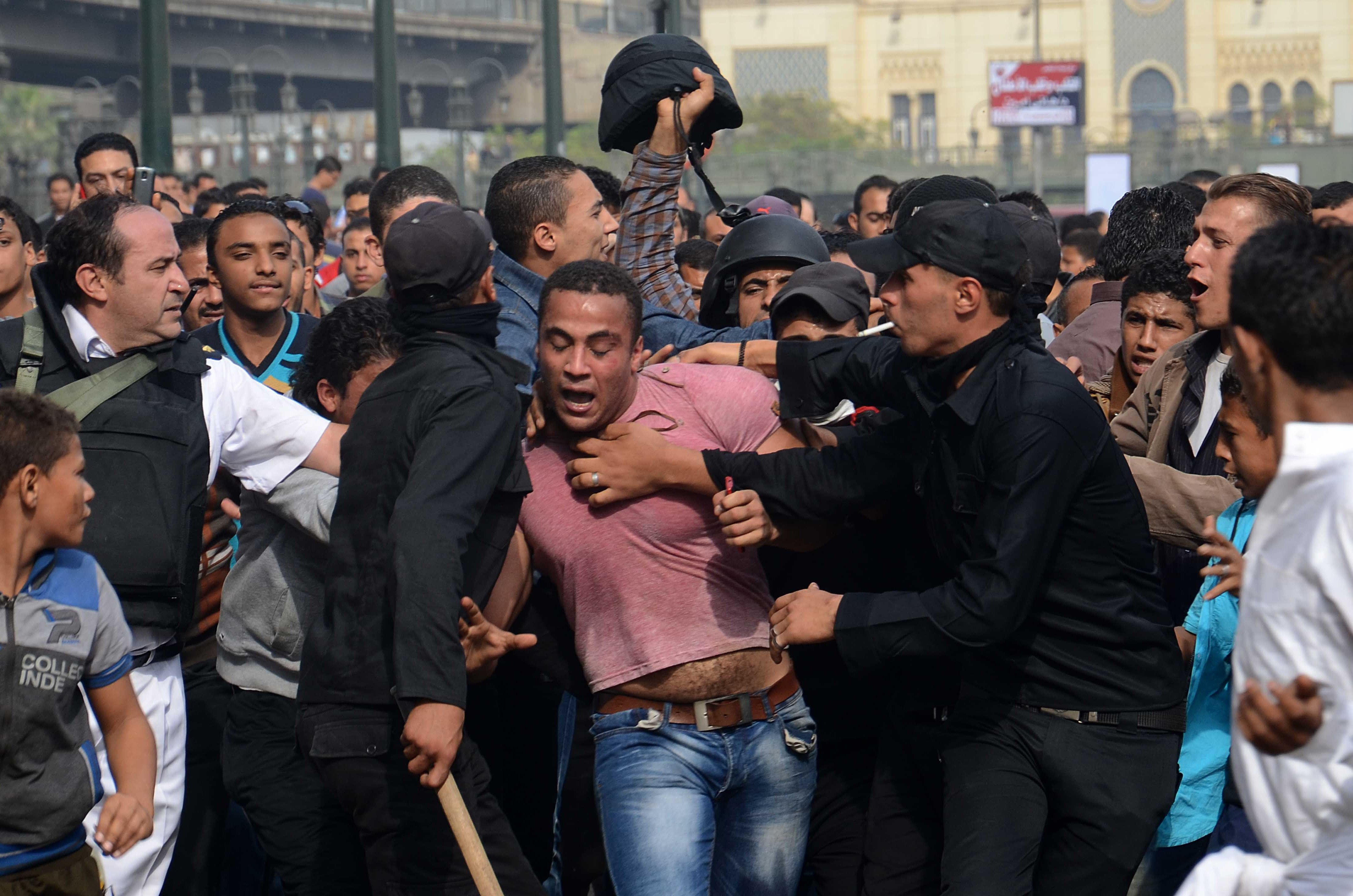 Egyptian policemen arrest a supporter of ousted president Mohamed Morsi during a protest in Ramses Square on the first day of Morsi's trial on November 4, 2013 in Cairo. (AFP PHOTO / MOHAMED ABDELWAHAB)