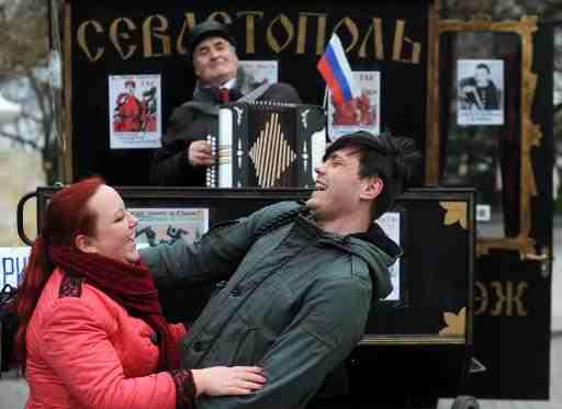 A man plays accordion as people dance during celebrations in Sevastopol on March 17, 2014  (AFP, Viktor Drachev)