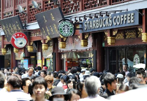 Pedestrians make their way past a Starbucks coffee shop in a street in the Chinese city Shanghai's old town on May 29, 2009 (AFP/File, Oliver Lang)
