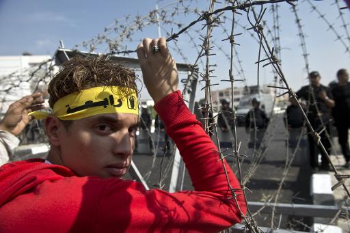 A supporter of Mohamed Morsi stands behind barbed wire outside the Police Academy where Morsi's trial began in Cairo on November 4, 2013 (AFP, Khaled Desouki)
