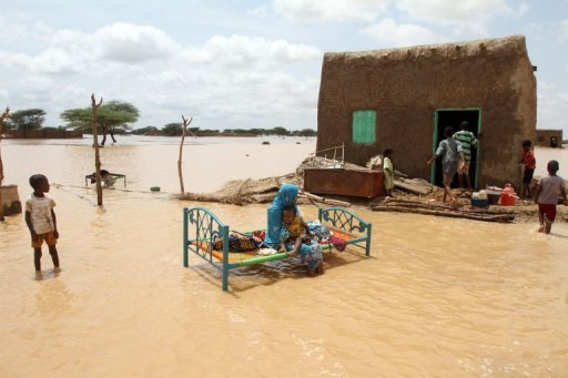 A Sudanese woman sits with her child next to her house in a flooded street on the outskirts of Khartoum, August 10, 2013 (AFP/File, Ashraf Shazly)