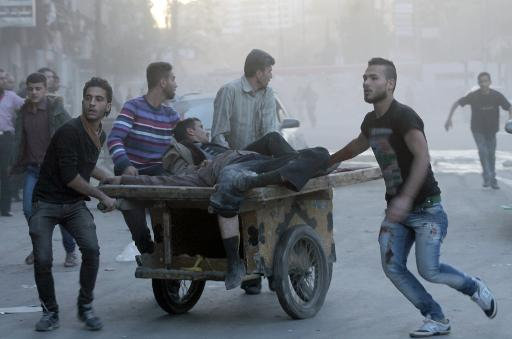 Two injured men are transported on a fruit barrow in the Syrian city of Aleppo, following shelling as fighting between pro-government forces and rebels continues on October 26, 2013 (Karam al-Masri/AFP/File, Karam al-Masri)