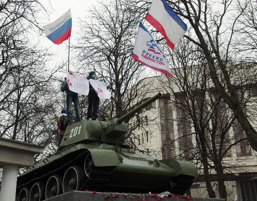 "Pro-Russian demonstrators hold placards reading ""Crimea for peace"" as they stand on a T-34 Soviet tank -- set as a WWII monument -- outside the Crimean parliament in Simferopol, on 27 February, 2014 (AFP, Vasiliy Batanov)"