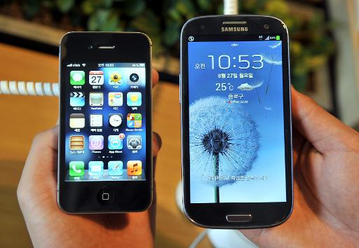 An employee shows an Apple's iPhone 4s (L) and a Samsung's Galaxy S3 (R) at a mobile phone shop in Seoul on August 27, 2012  (AFP/File, Jung Yeon-Je)