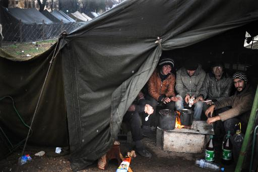 Refugees warm their hands on a bonfire in a tent during the first snowfall in a refugee camp set in the Bulgarian town of Harmanli, south-east of Sofia, on November 27, 2013 (AFP/File, Nikolay Doychinov)