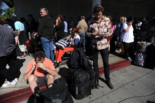 Passengers sit on the curb at Los Angeles International Airport on November 1, 2013 after a gunman reportedly opened fire at a security checkpoint (AFP, Robyn Beck)