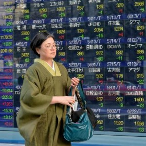 A woman walks past an electronic share prices board in Tokyo stocks Daily News Egypt