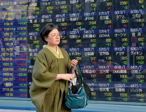 A woman walks past an electronic share prices board in Tokyo on March 3, 2014  (AFP, Yoshikazu Tsuno)