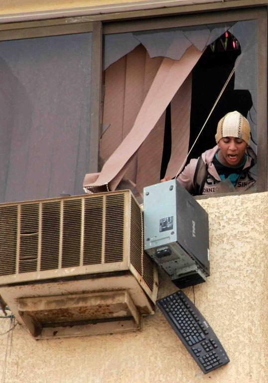 An Egyptian student at the Al-Azhar University throws a computer out of a window during a protest in Cairo, on October 30, 2013  (AFP Photo)