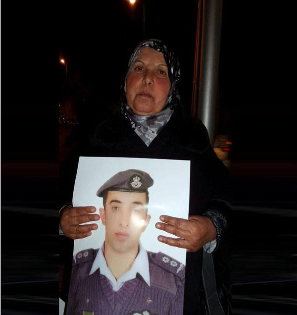 Mother of Jordanian pilot Muath Al-Kasasbeh holding his poster in a solidarity march last night at his birth town Al-Karak, after the spread of video showing his execution. (Public Domain)