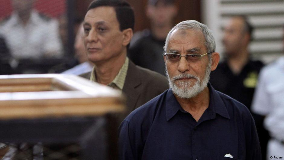 MB Supreme Guide Badie waves from inside the defendants cage during the trial of Brotherhood members on 3 February  2014 (AFP Photo)