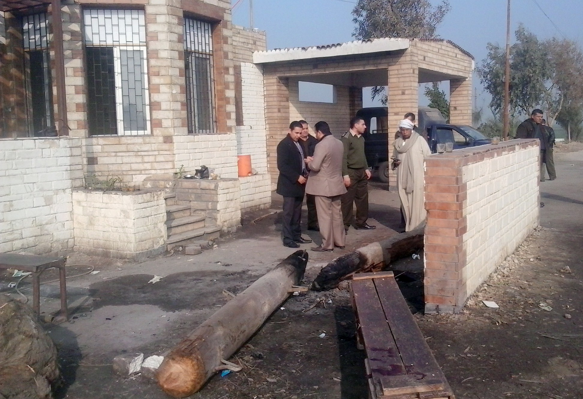 Egyptians inspect the attacked checkpoint in  Beni Suef on 23 January 2014. (AFP Photo)