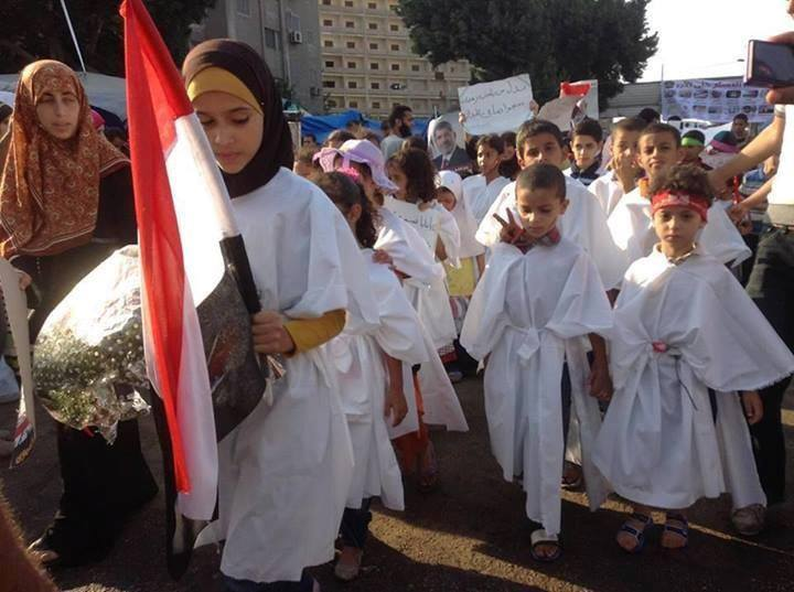 This photo of children dressed in shrouds in pro-Morsi rally went viral on social networks and sparked local and international criticism (Public domain photo)