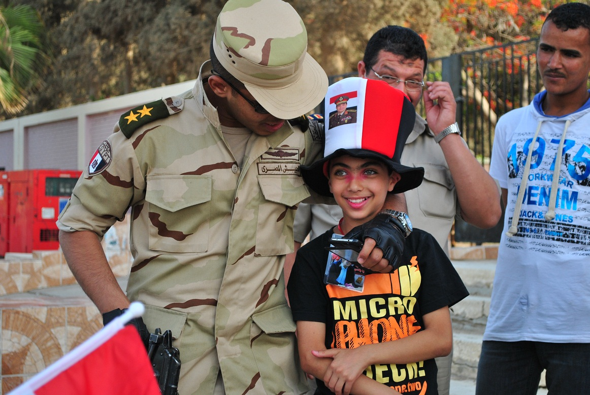 In Egypt, the military is trusted because of its construed Egyptian-ess, and all that is against the military is perceived as 'non-Egyptian' or 'anti-Egyptian'. In this photo, a military soldier poses with a child outside voting polls during elections on the constitution in June 2014. (Photo by: Jihad Abaza)