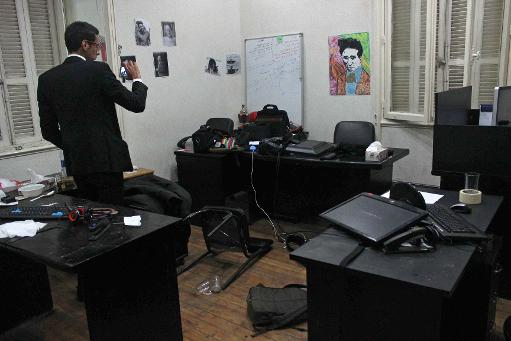 A picture taken on December 19, 2013 shows an Egyptian man taking photos of the offices of the Egyptian Centre for Economic and Social Rights in Cairo following a raid by police  (AFP Photo)