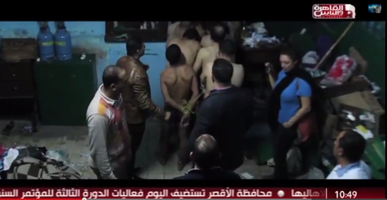 Snapshot from Al-Qahera w Al-Nas TV channel showing the defendants arrested and tied by the police, while journalist Mona Iraqi is filming the incident