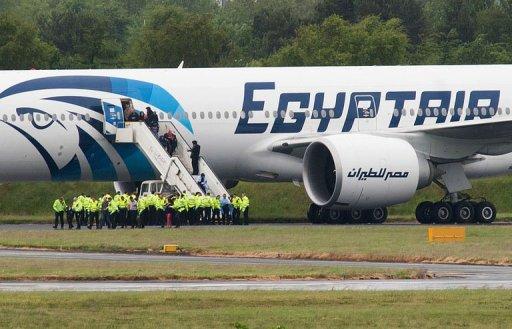 Police escort passengers off the Egyptair Boeing 777 flight Glasgow Prestwick airport in Scotland on June 15, 2013 (AFP, Andy Buchanan)