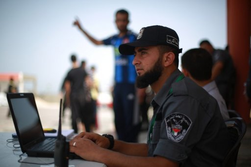 A Hamas policeman sits at his laptop in Gaza City on June 2, 2013 (AFP/File, Mohammed Abed)