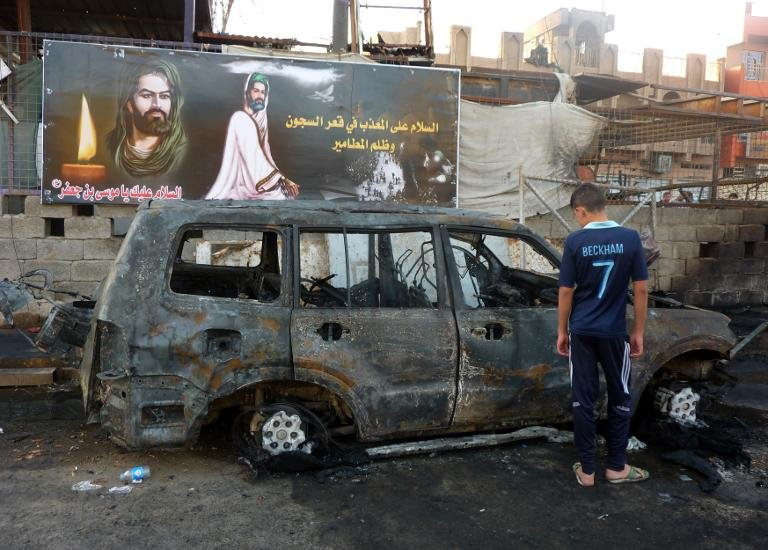 An Iraqi boy inspects a burnt out vehicle the day after a bombing in the Sadr city of Baghdad on 22 September 2013 (AFP Photo)