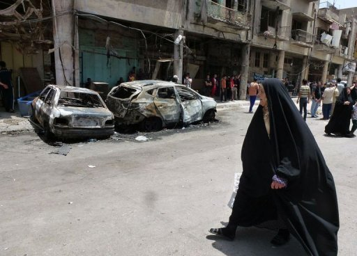 An Iraqi woman walks past burnt vehicles and damaged buildings on May 28, 2013, in Baghdad (AFP/File, Sabah Arar)