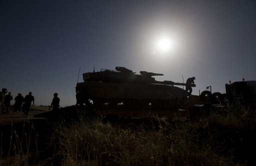 Israeli soldiers stand near a Merkava tank stationed in the Golan Heights near the Quneitra crossing, on June 6, 2013 (AFP, Ahmad Gharabli)