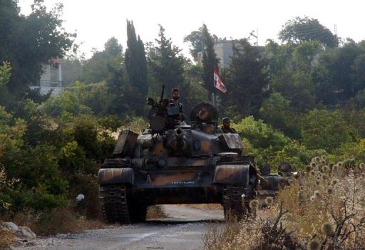 Syrian army tanks pursue opposition fighters in Latakia province, on August 8, 2013 (SANA/AFP/File)