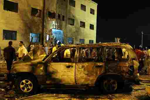 People gather near a burned-out vehicle after an attack outside the courthouse in Benghazi on July 28, 2013  (AFP/File, Abdullah Doma)