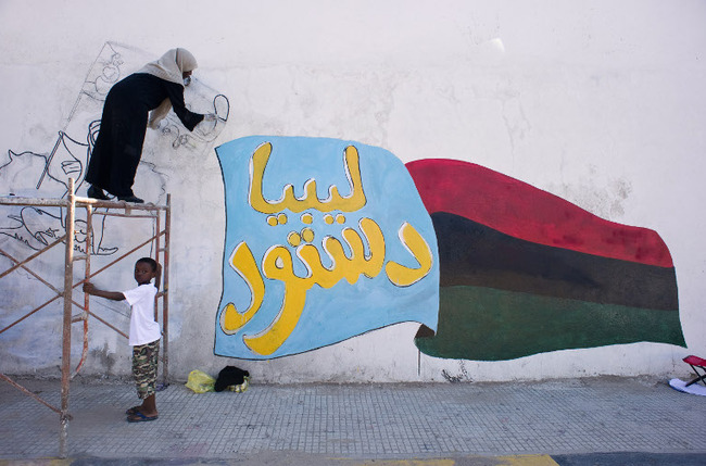 A young art student paints a mural reading '' Libyan constitution'' near a major road in central Tripoli. (AFP Photo)