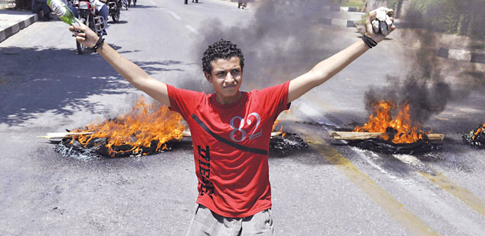 A protester carries stones in one hand and a bottle in the other as he kneels in front of burning tyres outside the governorate building in Luxor on 19 June 2013 (AFP Photo).