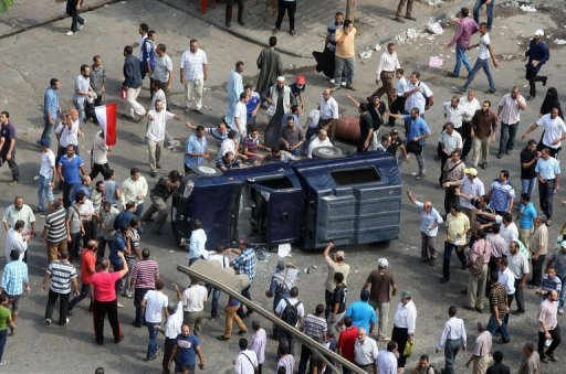 Muslim brotherhood supporters overturn a police vehicle in Cairo on August 14, 2013 (AFP, -)