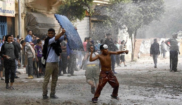 A young Egyptian protester throws a stone at anti riot policemen during clashes in the Cairo′s Mohammed Mahmoud street on November 22, 2012. (AFP File Photo)
