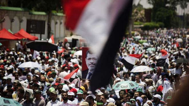 Egyptian Islamist groups led by the ruling Muslim Brotherhood take part in a demonstration to mark the upcoming one year anniversary since President Mohamed Morsi (portrait) was elected, on June 21, 2013 in Cairo. (AFP Photo)